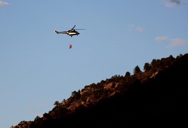 un helicoptero se dirige al incendio, esta tarde