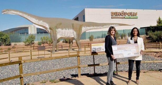 Imagen del momento de la entrega del cheque, que ha tenido lugar en la nueva zona temática del parque 'Tierra Magna' (a la izqda. Ana Belén Marco, presidenta de ASAPME Teruel y drcha. Higinia Navarro, Dtra-gerente de Dinópolis).